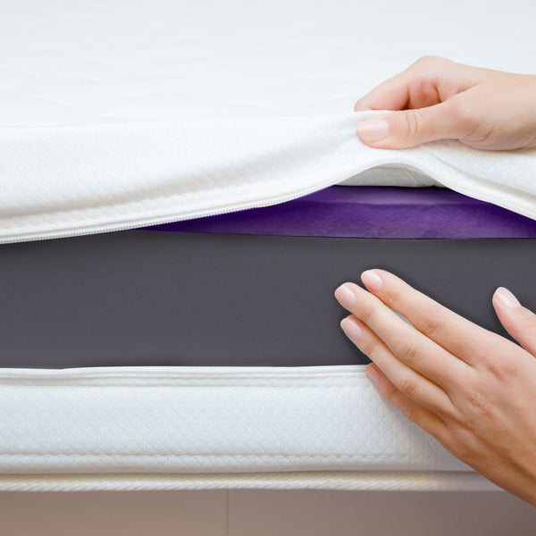 close up of hands putting a mattress protector on a mattress