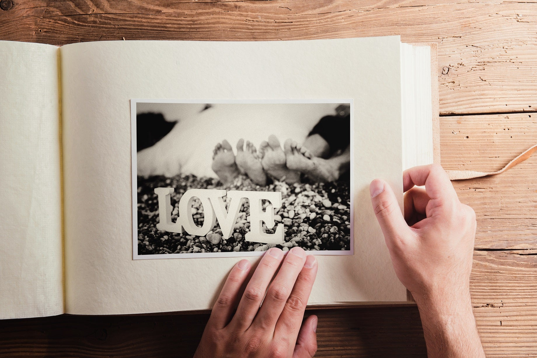 "man turns page of photo book ; image of the word ""love"""