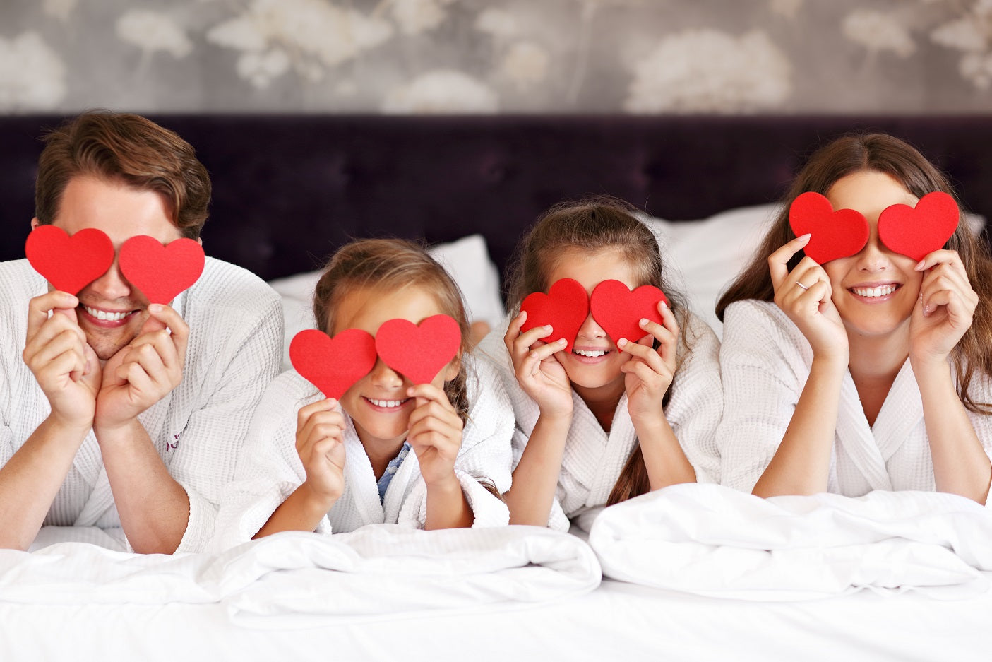 Family of 4 lay on bed holding hearts over eyes