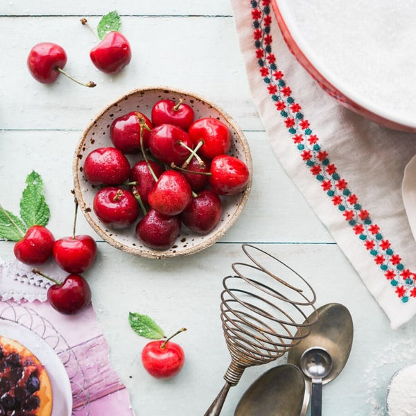 close up of tart cherries on a white wooden table