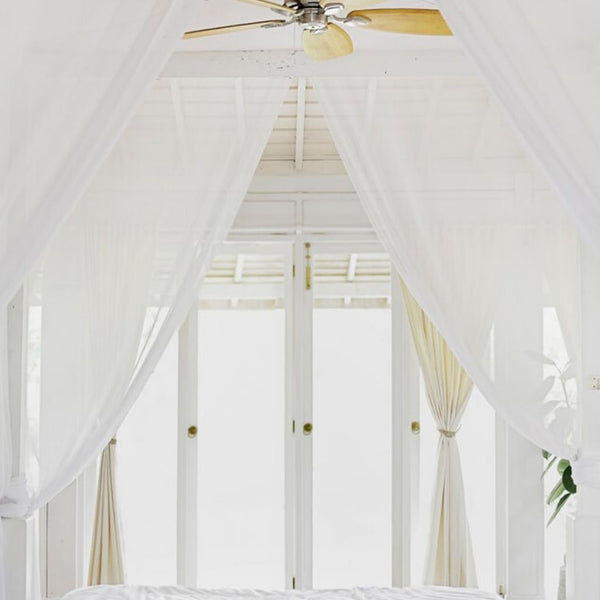 close up of a white canopy bed facing white french doors