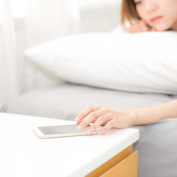 close up of a woman lying in bed turning off her phone on her bedside table