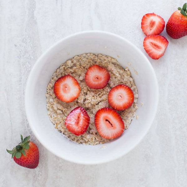 bowl of oatmeal covered in strawberries