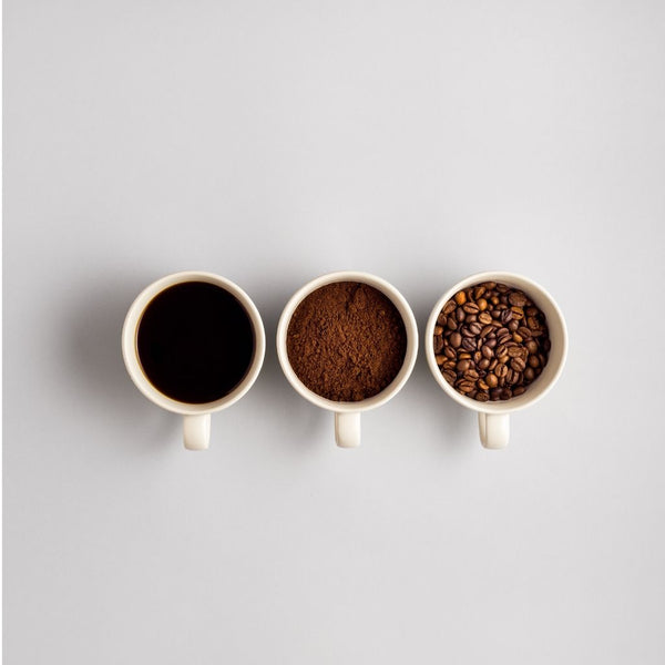 Close up of three white cups; one of a cup of coffee, the second with ground coffee, the third with coffee beans