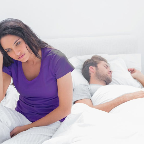 close up of a young woman sitting up in bed wearing a purple shirt next to a man sleeping