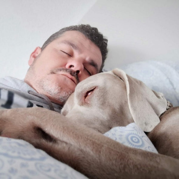 close up of a man in his 40's sleeping in bed with his dog
