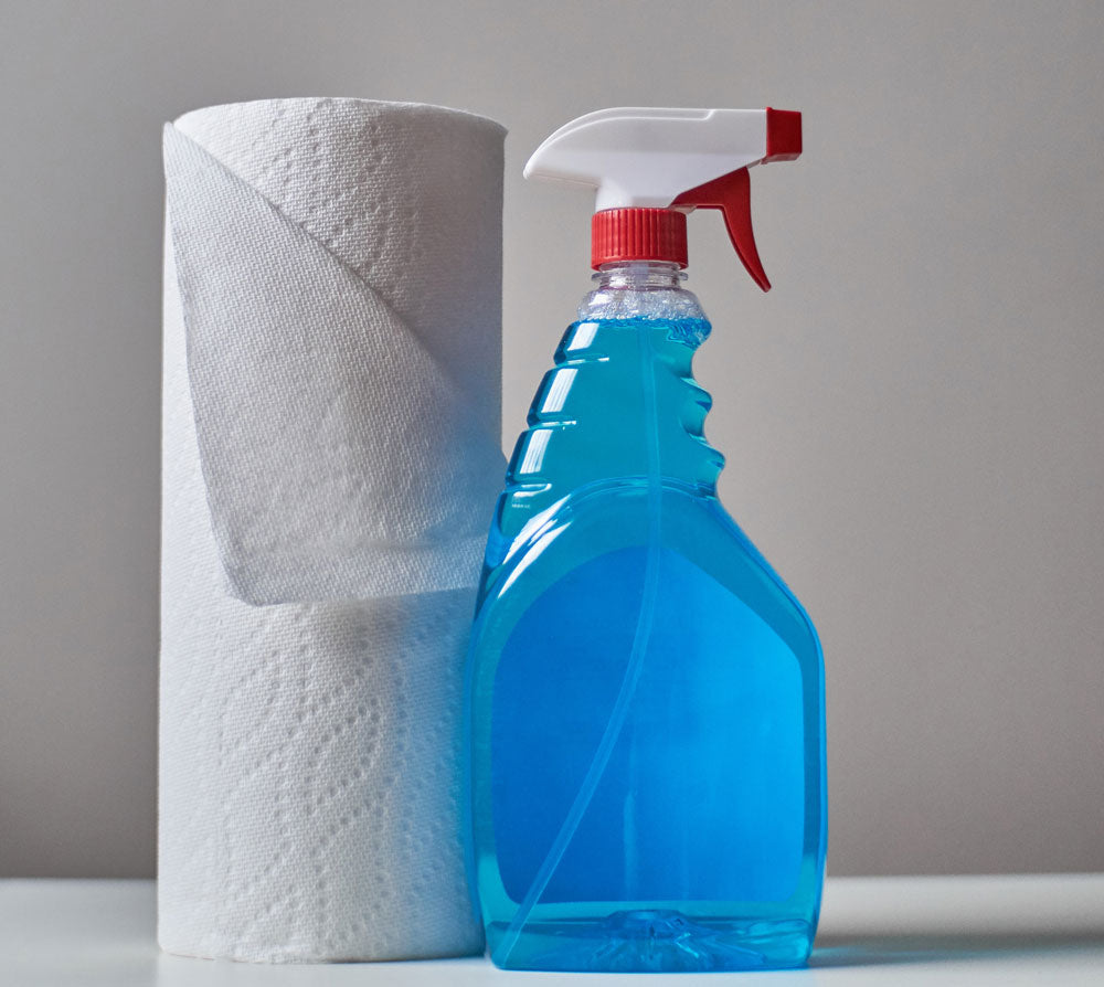 Cleaning product beside paper towel role.