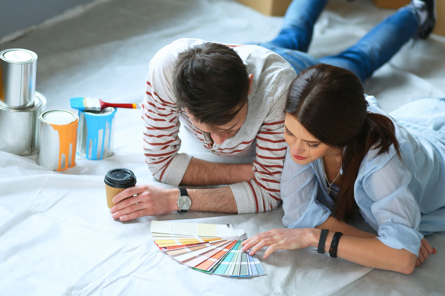 man and woman lay on floor choosing paint colours for bedroom