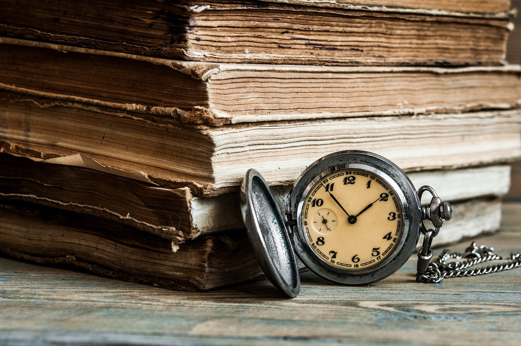 old books and silver pocket watch showing time 1:55