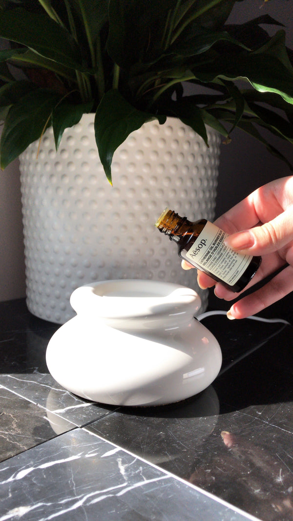 Woman pours essential oil into diffuser for better sleep