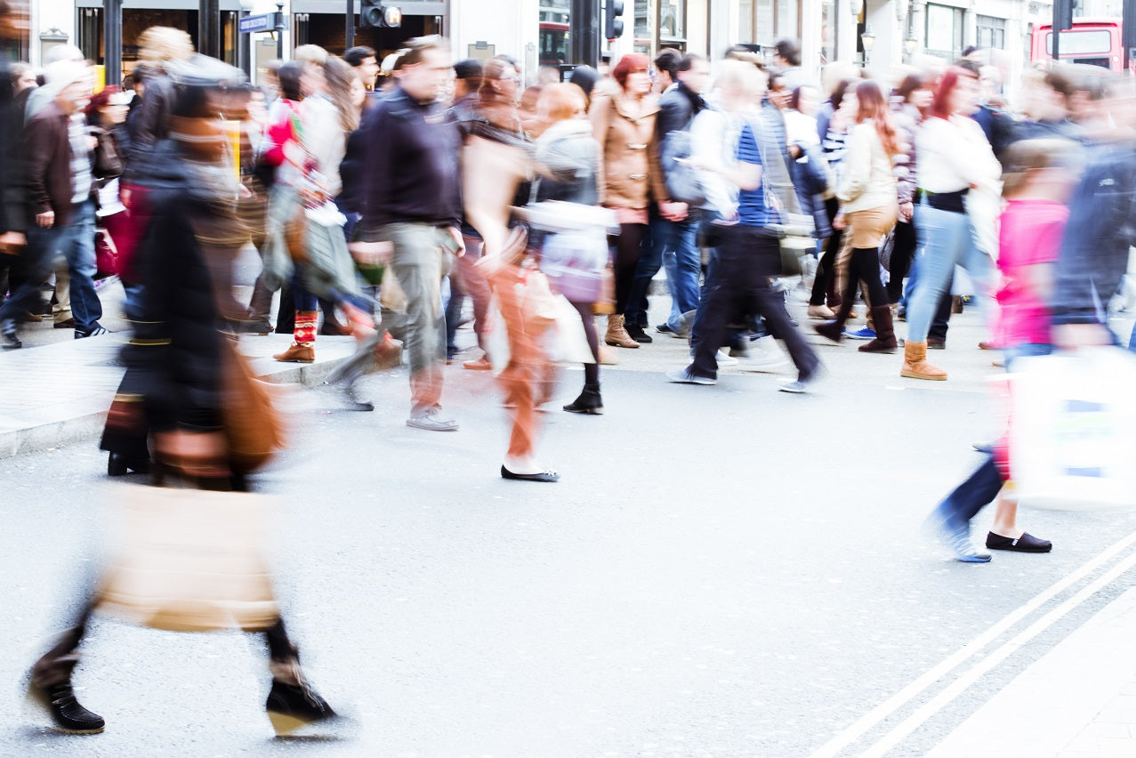 Blurred image of people crossing busy, noisy street