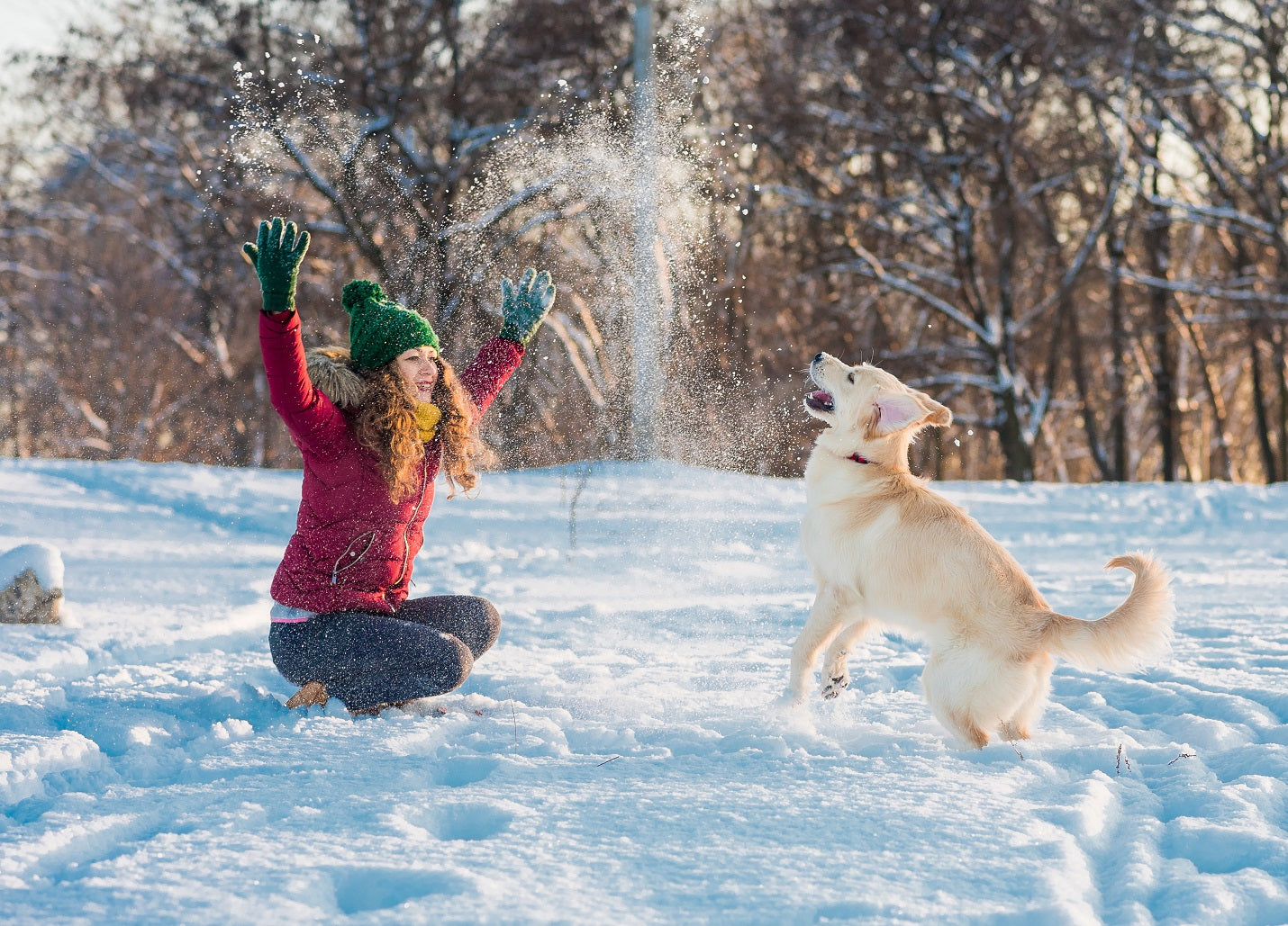 woman plays with dog in snow to get exercise to overcome SAD