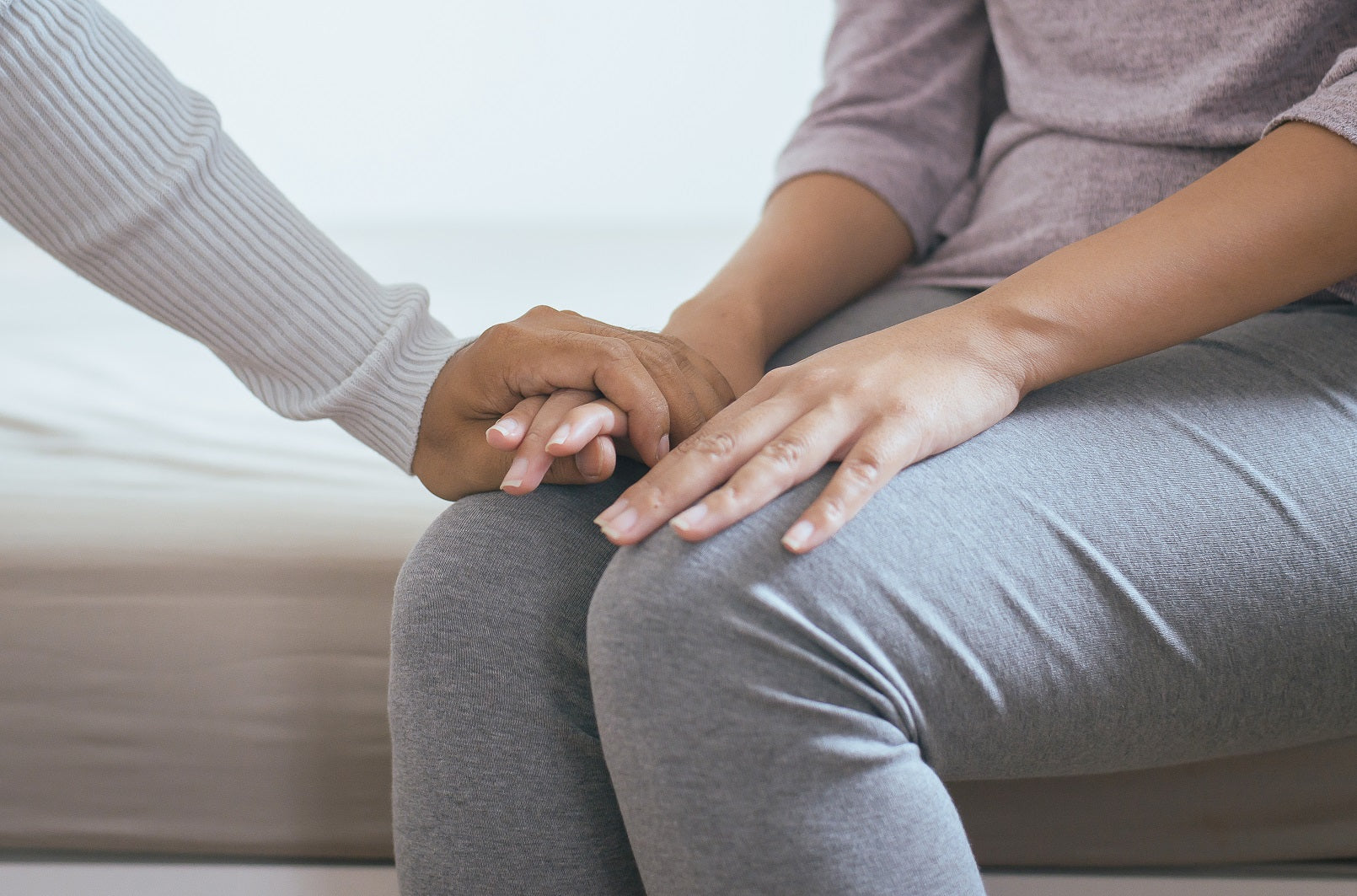 Two people hold hands at doctor's office