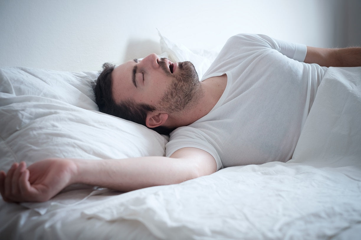man in white t-shirt sleeps on bed with white sheets