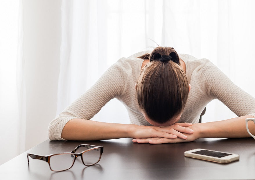 woman rests head on hands on desk with glasses and phone; exhausted from sleep apnea
