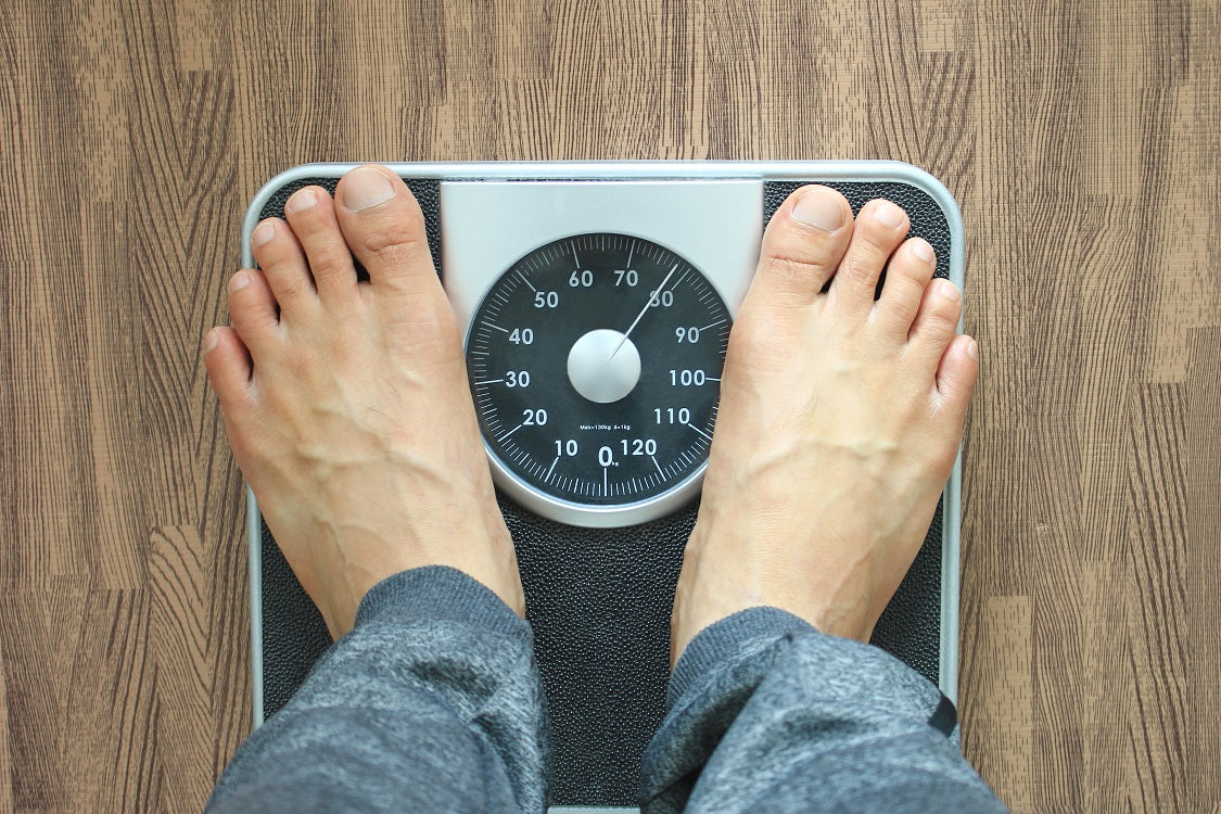 man's feet standing on weight scale on wooden floor