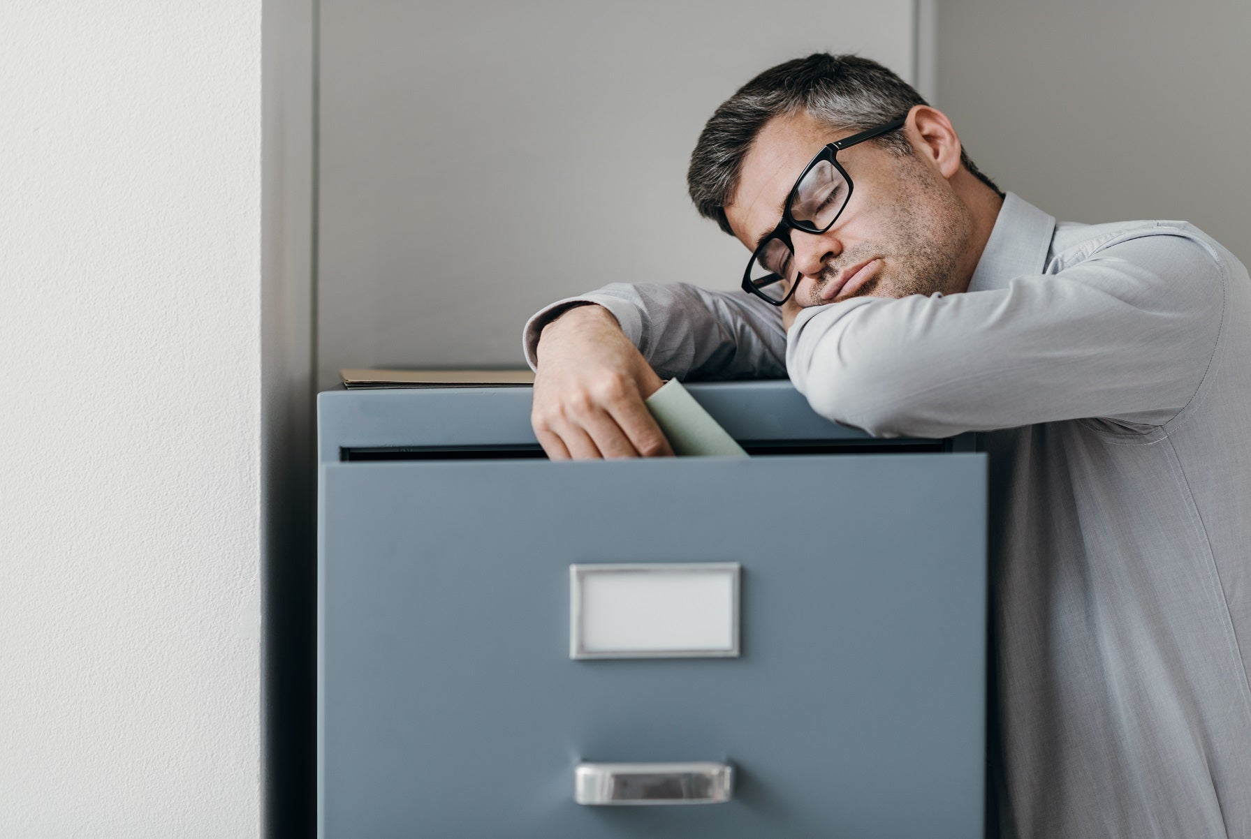 narcoleptic man with glasses asleep on filing cabinet