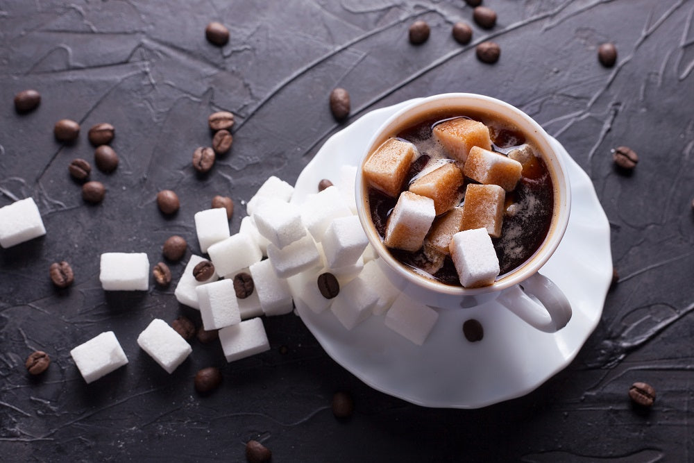 Chocolate, coffee, sugar cubes in a white cup on a saucer