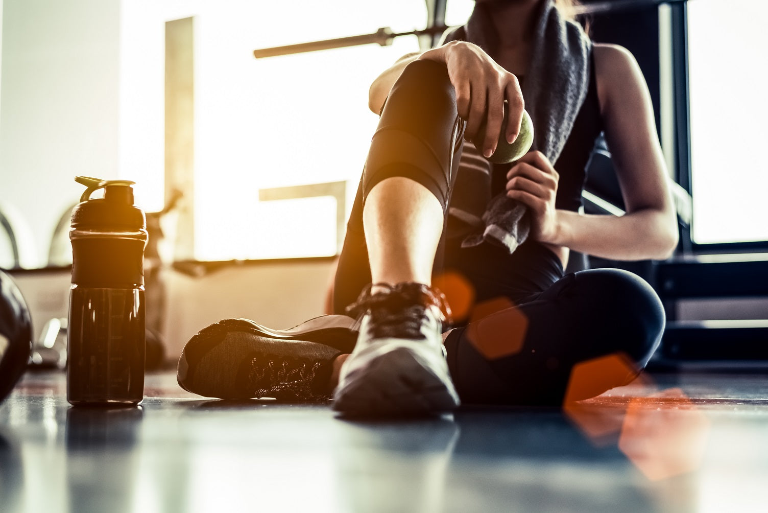 woman sits on floor after workout with apple and water bottle