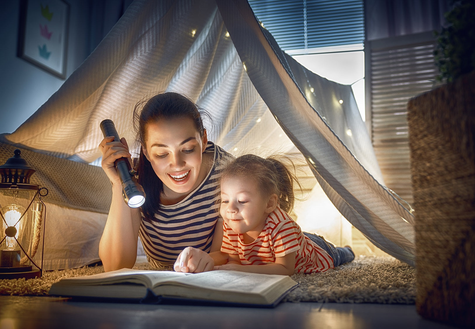 woman in blanket tent holds flashlight to read book to little girl