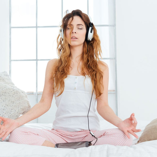 close up of young women sitting on top of a bed listening to music and doing yoga