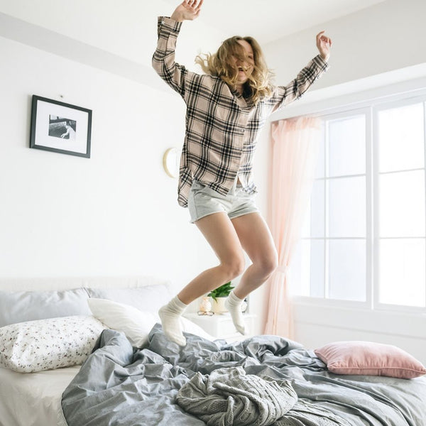 young women jumping on bed