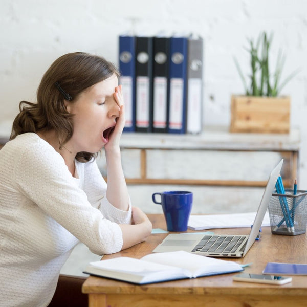 Middle-aged women sitting at a desk while yawning