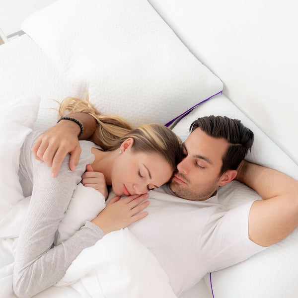 Close up of a young couple sleeping in each other's arms on a PerfectSense Mattress and PerfectSense Memory Pillows