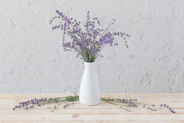 lavender bouquet in white vase on wooden table