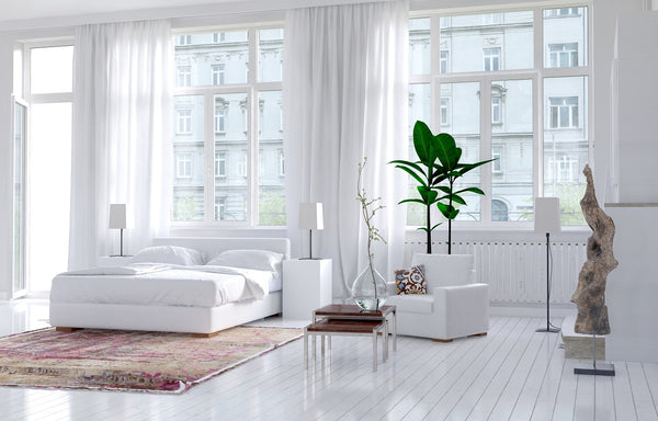 modern, white bedroom with rug under double bed