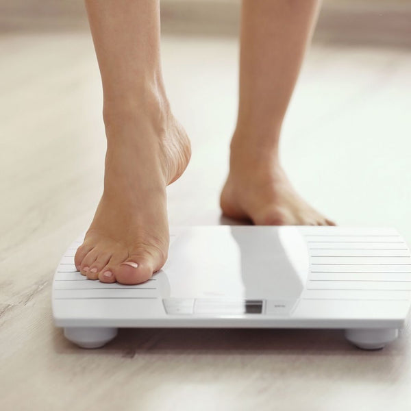 Women stepping onto a weighing scale