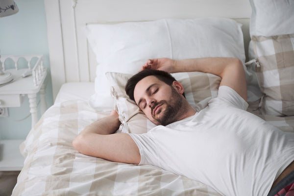 single man in white shirt sleeping on double bed