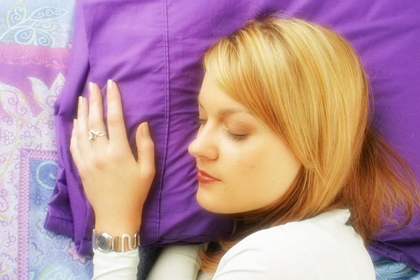 blond woman sleeps with head on pillow