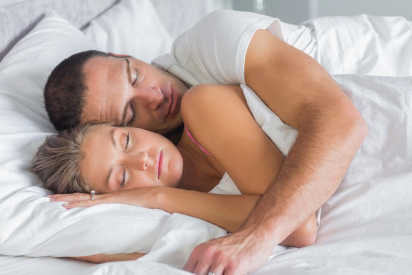 man and woman spooning while they sleep