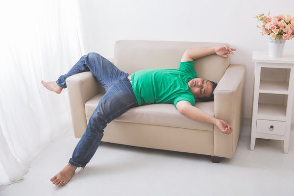 man sleeps in starfish position on couch
