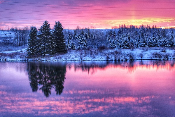 pink sky at dusk behind snow-covered hill reflecting on water