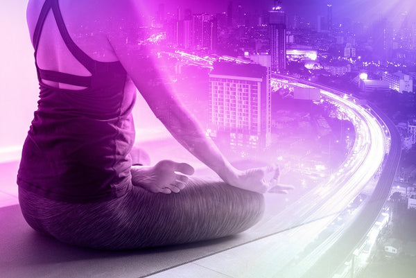 Woman meditates overlooking busy cityscape to relieve sleep paralysis