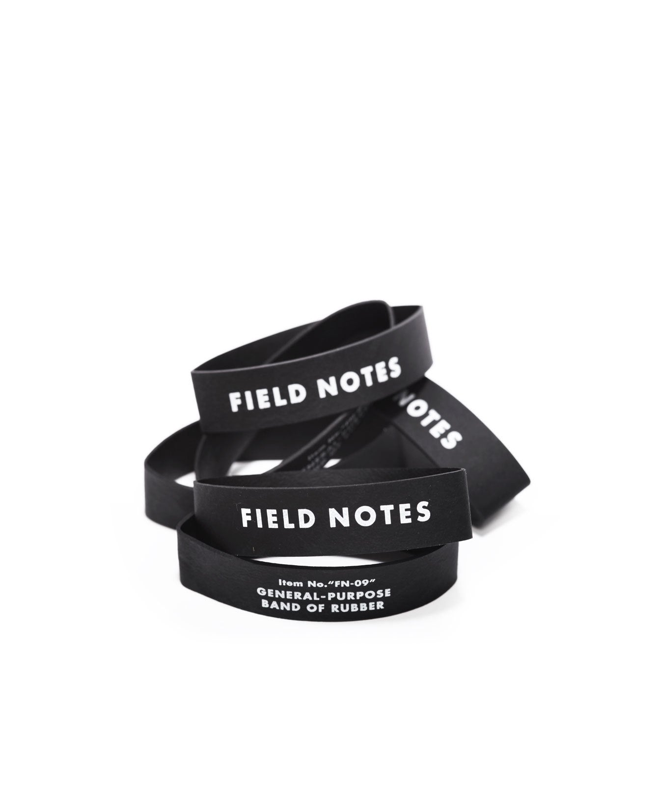 "A pile of 3"" by 5/8"" black rubber bands with Field Notes logo in white ink."
