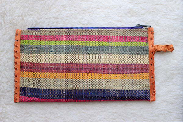 muted multi-colored striped raffia woven clutch with leather trim