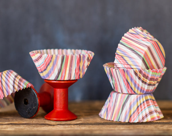 multicolored striped paper cupcake liners for a circus party supplies