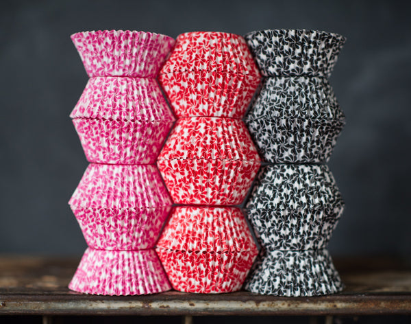 hot pink, red, black, and white pinwheel flower printed paper cupcake liners