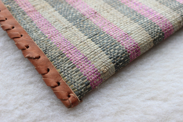 pink, green, and cream striped raffia woven clutch with leather trim