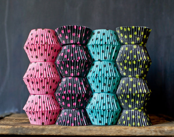 pink, turquoise, black, and neon green polka dot paper cupcake liners