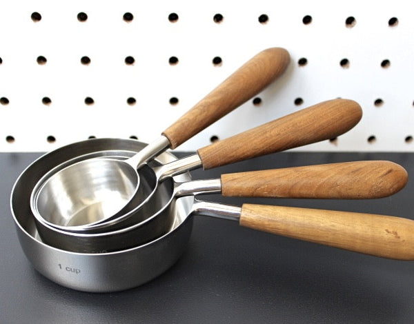 teak wood and stainless steel measuring cups for a simple utilitarian kitchen