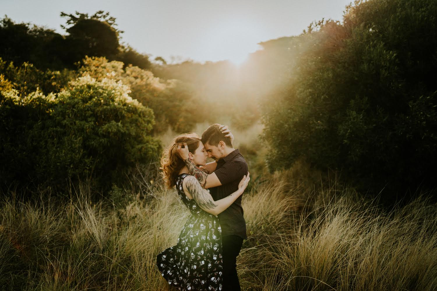 couple embracing with the sun setting behind them