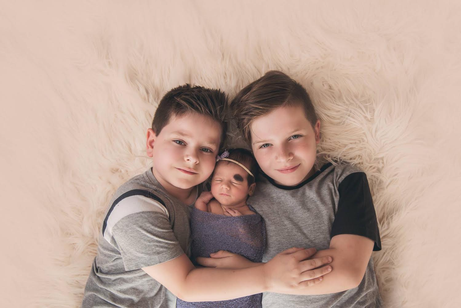 Sibling photography brothers with newborn sister
