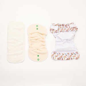 flatlay of bamboo and hemp inserts and open newborn nappy shell