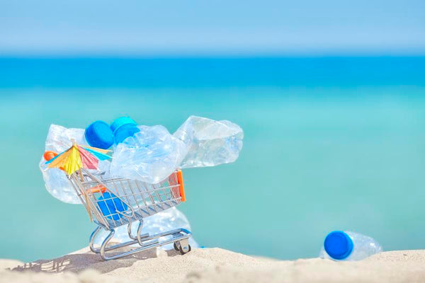 Plastic bottles in shopping cart on beach