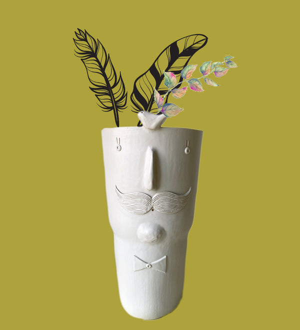 Sculpted planter pot in shape of man with moustache and bowtie on mustard background with leaf graphics