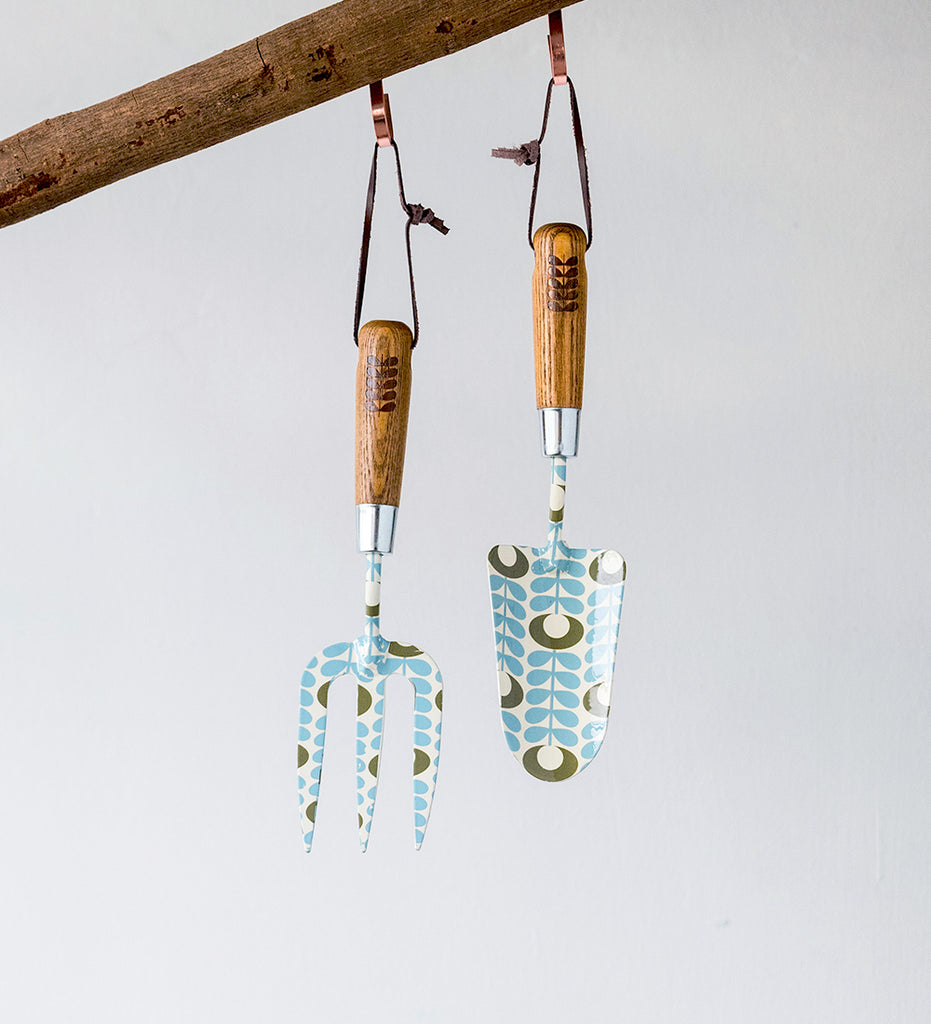 Patterned gardening tools with leather strap hanging from log
